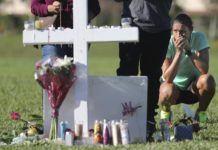 Maria Creed is overwhelmed with emotion as she crouches in front of one of the memorial crosses at Pine Trails Park in Parkland, Fla., Friday, Feb. 16, 2018, that were placed for the victims of the Wednesday shooting at Marjory Stoneman Douglas High School. Creed's son, Michael Creed, is a sophomore at the school. (Amy Beth Bennett/South Florida Sun-Sentinel via AP)