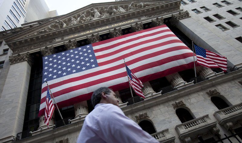 In this Aug. 8, 2011 file photo, a pedestrian walks past the New York Stock Exchange in New York. (AP Photo/Jin Lee, File)