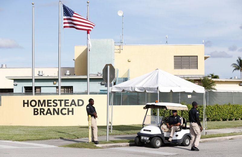 FILE: Security guards stand outside a former Job Corps site that now houses child immigrants, Monday, June 18, 2018, in Homestead, Fla. It is not known if the children crossed the border as unaccompanied minors or were separated from family members. An unapologetic President Donald Trump defended his administration's border-protection policies Monday in the face of rising national outrage over the forced separation of migrant children from their parents. (AP Photo/Wilfredo Lee/FILE)