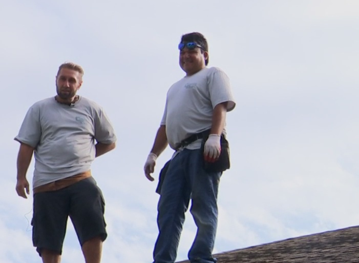 Robert Coszey and Orlis Hernandez enjoy the cooler weather while they labor outside. Photo via WINK News.