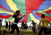 Elementary school third graders run under a rainbow colored tarp during Fitness Day. Photo via AP.