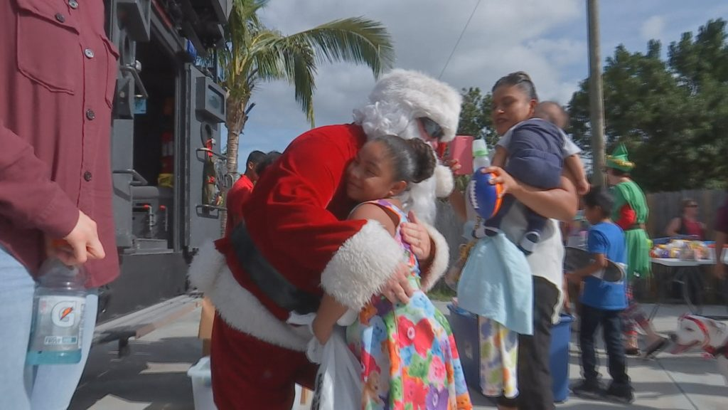 A child gives Santa a hug. Photo via WINK News.