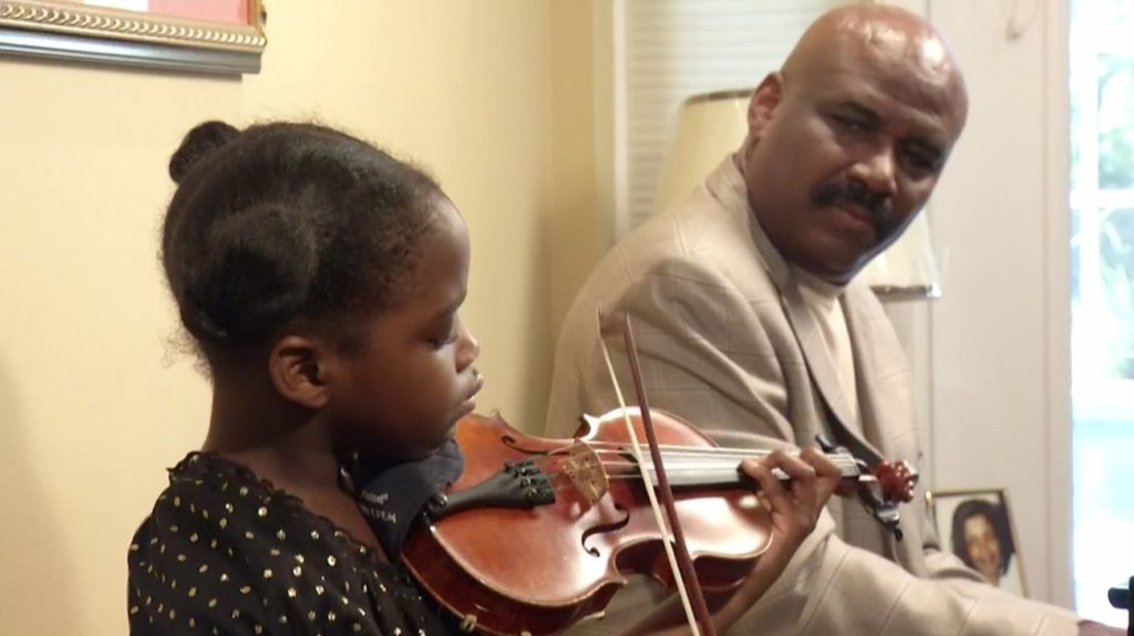 A daughter plays an instrument as her father looks upon. Photo via Ivanhoe Newswire.