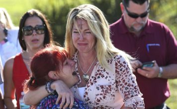 Parents wait for news of their loved ones after a mass shooting at Marjory Stoneman Douglas High School in Parkland, Fla., on Feb. 14, 2018. (AP Photo/Joel Auerbach)