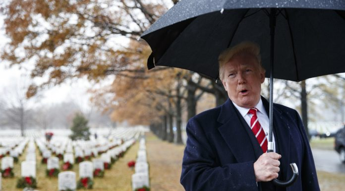 President Donald Trump speaks to media he visits Section 60 at Arlington National Cemetery in Arlington, Va., Saturday, Dec. 15, 2018, during Wreaths Across America Day. (AP Photo/Carolyn Kaster)