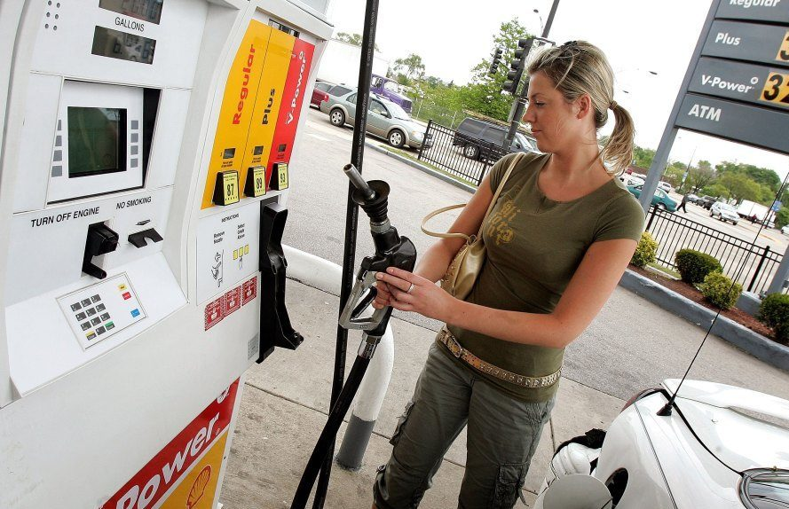 A motorist replaces the gas pump after filling her car at a Shell station. Photo via CBS.