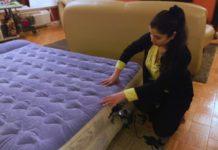 Woman sets up an air mattress. Photo via Consumer Reports.