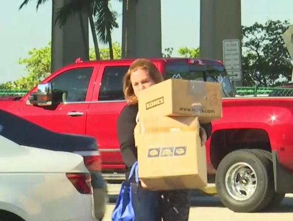 Carrie Ehrlich takes packages to the post office. Photo via WINK News.