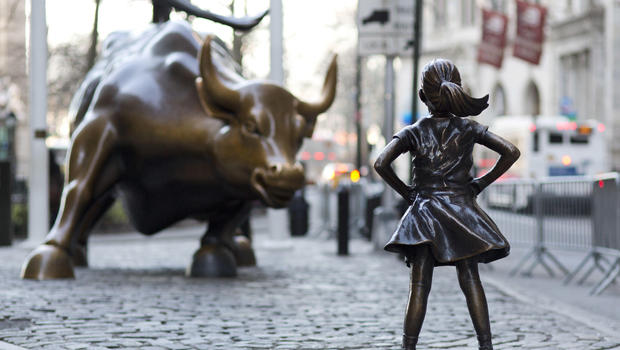 The fearless girl stands before the iconic Wall Street