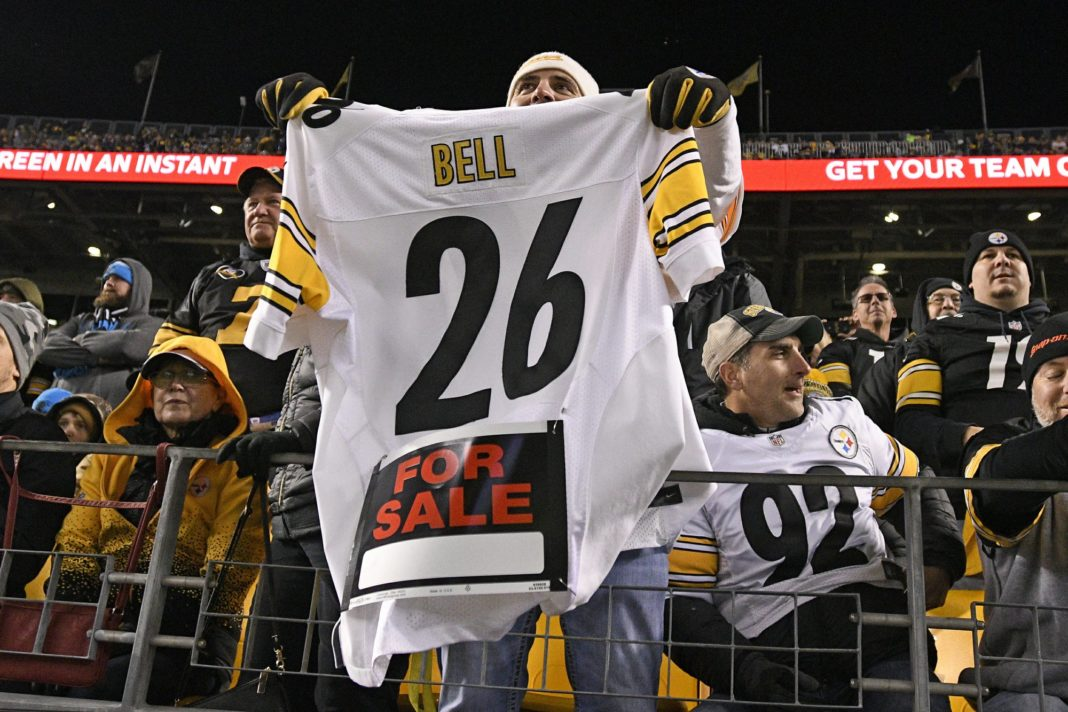 FILE - In this Nov. 8, 2018, file photo, a Pittsburgh Steelers fan holds a Le'Veon Bell jersey during the second half of an NFL football game between the Steelers and the Carolina Panthers in Pittsburgh. The steady exodus of mid-level veterans from the NFL is one element of a long-standing tension between players and the league over the structuring of contracts. The contract holdouts by Bell and Earl Thomas this season put the issue into vivid focus. (AP Photo/Don Wright, File)