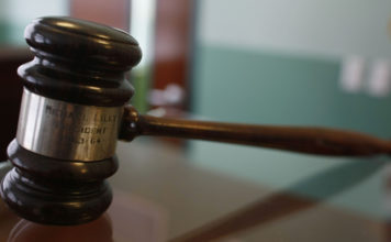 A judges gavel rests on top of a desk in the courtroom. Photo via CBS News.