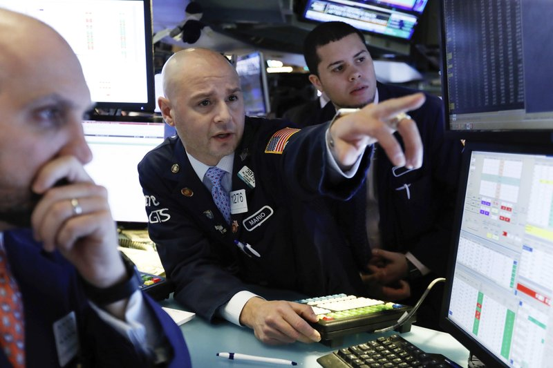 In this Jan. 4, 2019, file photo Mario Picone, center, works with fellow specialists on the floor of the New York Stock Exchange. Photo via AP/Richard Drew.