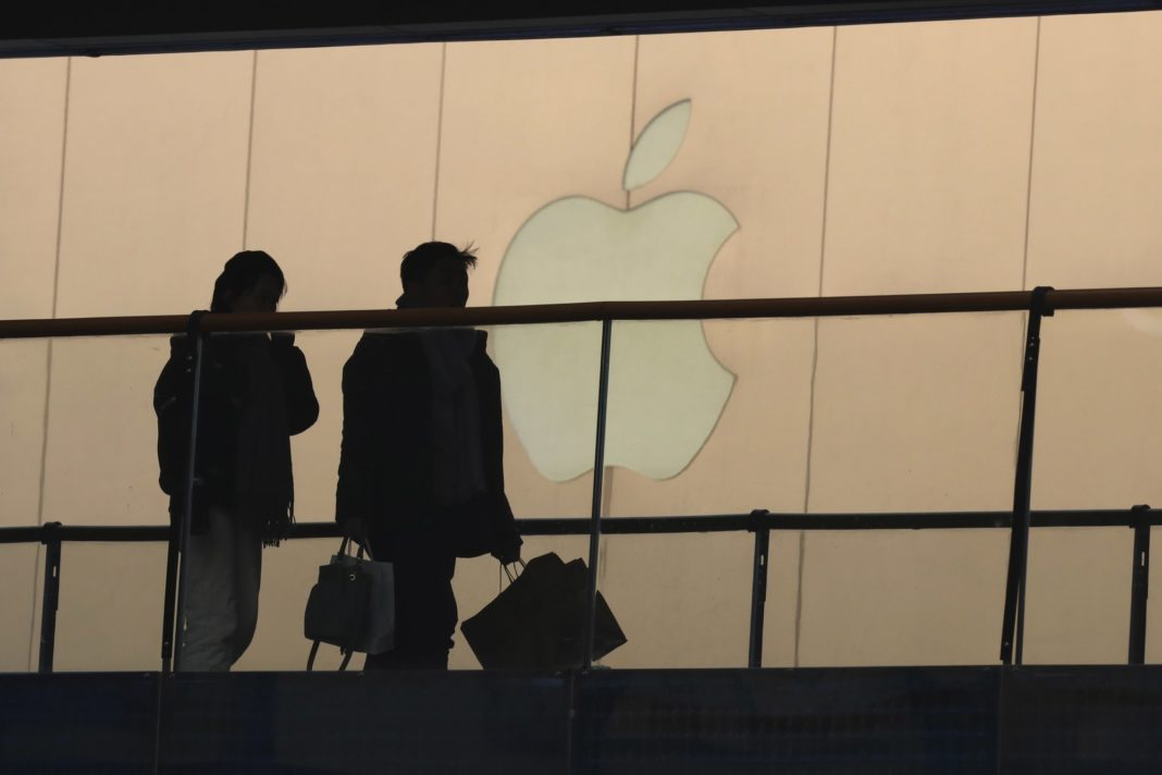 In this Thursday, Jan. 3, 2019, photo, shoppers pass by the Apple store logo at a shopping mall in Beijing. A U.S. delegation led by deputy U.S. trade representative, Jeffrey D. Gerrish arrived in the Chinese capital ahead of trade talks with China. China sounded a positive note ahead of trade talks this week with Washington, but the two sides face potentially lengthy wrangling over technology and the future of their economic relationship. Photo via AP/Ng Han Guan.
