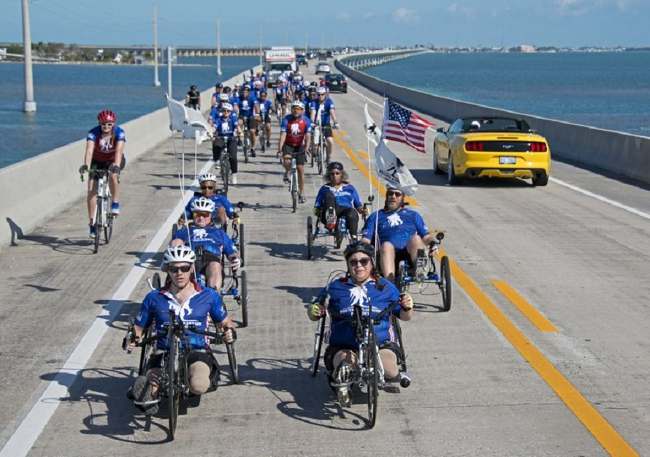 In this photo provided by the Florida Keys News Bureau, injured military personnel including Army Staff Sgt. Sam Oelke, left, retired Air Force Staff Sgt. Jennifer Caudillo, right, and other wounded military personnel ride bicycles on the Seven Mile Bridge during the Florida Keys Soldier Ride Friday, Jan. 11, 2019, near Marathon, Fla. Some 45 men and women are riding bicycles down segments of the Florida Keys Overseas Highway as a facet of an effort organized by the Wounded Warrior Project to raise public awareness and support for the needs of severely injured members of the U.S. military. Photo via AP.
