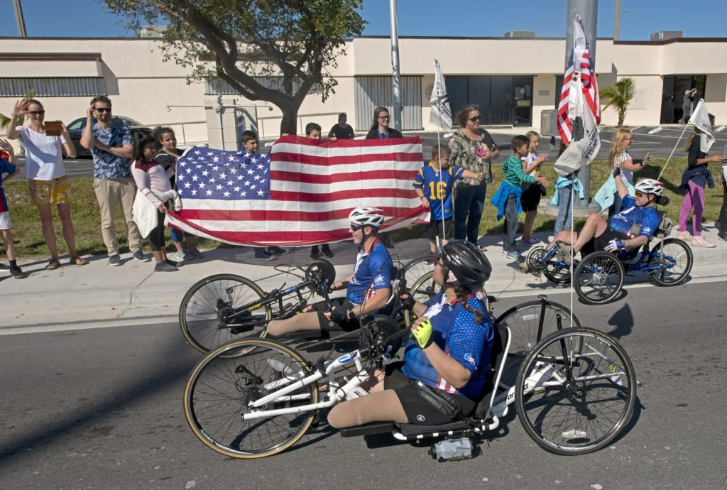 Injured military personnel ride bicycles by elementary school children and teachers during the Florida Keys Soldier Ride Friday, Jan. 11, 2019, in Marathon, Fla. Photo via AP.