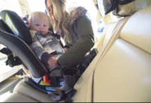 Mother properly secures child in car seat. Photo via CBS.