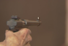 Person fires a gun. Photo via WINK News.