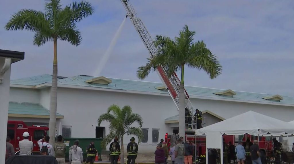 Rescue workers on the scene where a clubhouse was damaged by a fire. (WINK News photo)