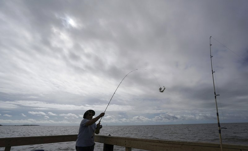In this Sept. 5, 2018 file photo, Tim Hitchens, of Gulfprort, Miss., pulls in a fish while fishing from a pier in the Gulf of Mexico, the morning after Tropical Storm Gordon made landfall nearby, in Biloxi, Miss. The rules that govern recreational marine fishing in the U.S. will get an overhaul due to a new law passed by in December. Photo via AP/Gerald Herbert.