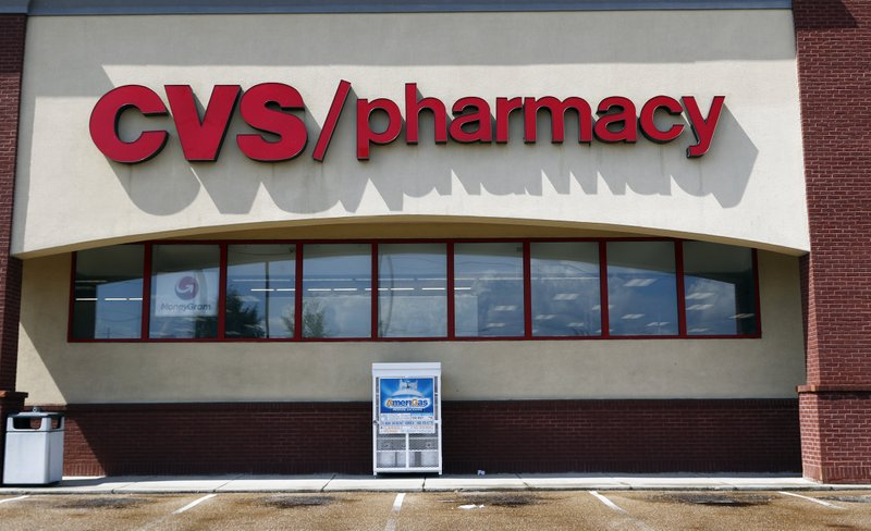 FILE- In this Aug. 7, 2018, file photo a CVS Pharmacy building sign rests on a Jackson, Miss., store. CVS Health topped fourth-quarter earnings forecasts, but the nation's second-largest drugstore chain also debuted a 2019 outlook that fell far short of Wall Street expectations. The company said Wednesday, Feb. 20, 2019, that it expects adjusted earnings to range between $6.68 and $6.88 this year. FactSet says analysts expect earnings of $7.35 per share. (AP Photo/Rogelio V. Solis, File)