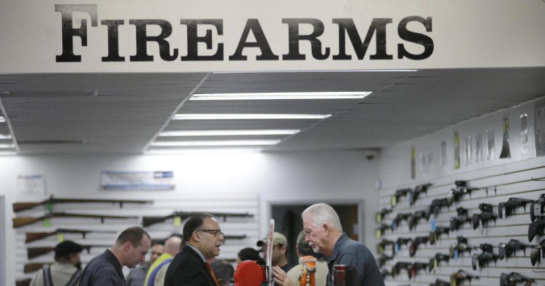 FILE - In this Dec. 9, 2015, file photo, sales associate Mike Conway, right, shows Paul Angulo a pistol at Bullseye Sport gun shop in Riverside, Calif. (AP Photo/Jae C. Hong, File)