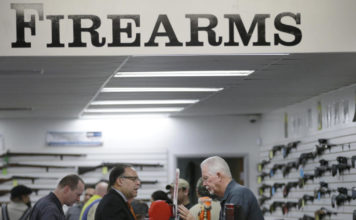 FILE - In this Dec. 9, 2015, file photo, sales associate Mike Conway, right, shows Paul Angulo a pistol at Bullseye Sport gun shop in Riverside, Calif. (AP Photo/Jae C. Hong, File)
