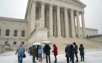 Visitors wait to enter the Supreme Court as a winter snow storm hits the nation's capital making roads perilous and closing most Federal offices and all major public school districts, on Capitol Hill in Washington, Wednesday, Feb. 20, 2019. The Supreme Court is ruling unanimously that the Constitution's ban on excessive fines applies to the states. The outcome Wednesday could help an Indiana man recover the $40,000 Land Rover police seized when they arrested him for selling about $400 worth of heroin. (AP Photo/J. Scott Applewhite)