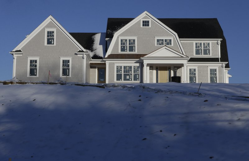 In this Thursday, Feb. 21, 2019 photo a recently constructed home is surrounded by snow in Natick, Mass. On Thursday, March 28, Freddie Mac reports on this week's average U.S. mortgage rates. (AP Photo/Steven Senne)