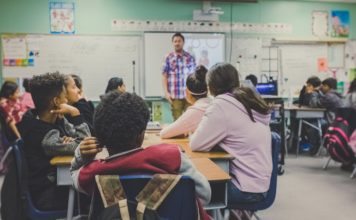 Man teaches classroom full of children. (Credit: Neonbrand Unsplash)