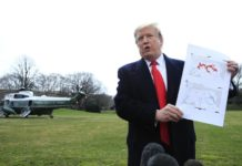 President Donald Trump shows a map of Syria and Iraq showing the presence of the Islamic State (IS) in 2017 and 2019, as he speaks to reporters before leaving the White House in Washington, Wednesday, March 20, 2019, for a trip to visit an Army tank plant in Lima, Ohio, and a fundraising event in Canton, Ohio. (AP Photo/Manuel Balce Ceneta)