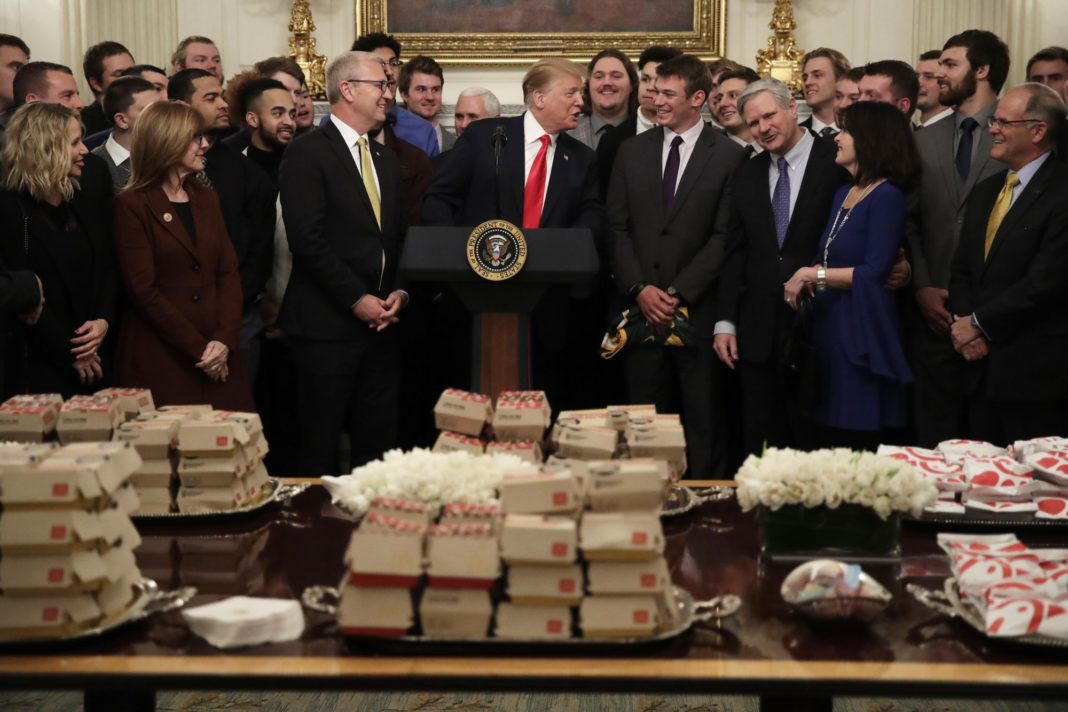 President Donald Trump welcomes the 2018 NCAA FCS College Football Champions, The North Dakota State Bison, to the State Dining room of the White House in Washington, Monday, March 4, 2019, with McDonald's and Chick-fil-A fast food. Fourth from left is Sen. Kevin Cramer, R-N.D., third right is Sen. John Hoeven, R-N.D., and fourth from right is North Dakota State Bison quarterback Easton Stick. (AP Photo/Carolyn Kaster)