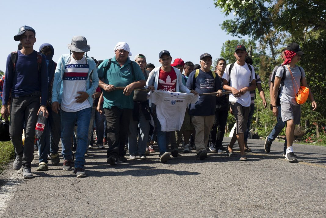 Central American migrants, part of a caravan hoping to reach the U.S. border, walk on a road in Frontera Hidalgo, Mexico, Friday, April 12, 2019. The group pushed past police guarding the bridge and joined a larger group of about 2,000 migrants who are walking toward Tapachula, the latest caravan to enter Mexico. (AP Photo/Isabel Mateos)