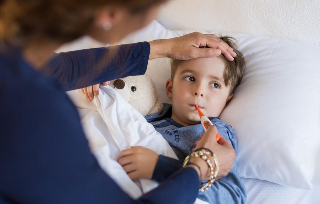 Sick boy laying in bed as his mother takes his temperature. (Credit: CBS News)