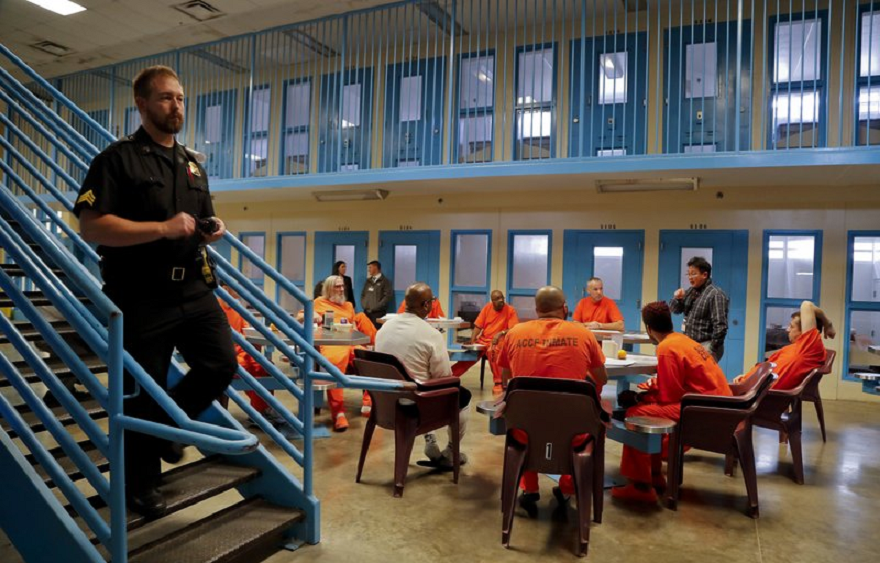 A guard makes his rounds checking cells as inmates gather for a session with Soldier On, Chaplain Quentin Chin inside the veteran's pod at the Albany County Correctional Facility, Monday, Nov. 27, 2017, in Albany, N.Y.(AP Photo/Julie Jacobson)