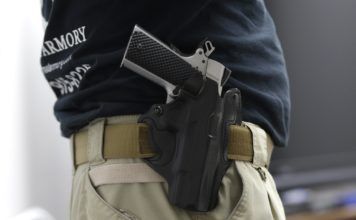 FILE - In this Jan. 5, 2016 file photo, Mike Weinstein, director of training and security at the National Armory gun store and gun range, wears a Ruger 1911 handgun in a holster as he teaches a concealed weapons permit class in Pompano Beach, Fla. Florida might grant authority to 2 million civilians who can lawfully carry guns tucked in waistbands, under jackets or inside purses into restaurants, shopping malls and elsewhere. (AP Photo/Lynne Sladky, File)