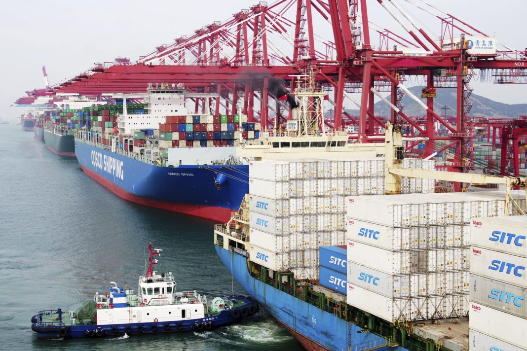 In this Wednesday, May 8, 2019, photo, a barge pushes a container ship to the dockyard in Qingdao in eastern China's Shandong province. (Chinatopix via AP)