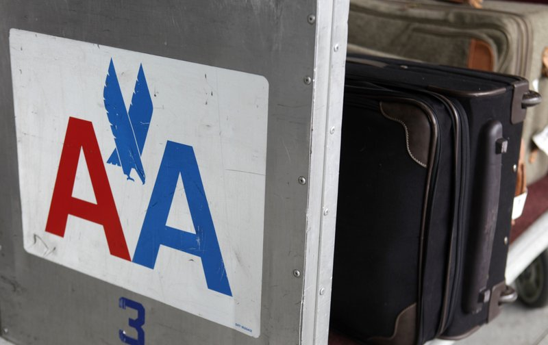 FILE - In this Nov. 29, 2011 file photo, an American Airlines symbol is displayed on the side of a luggage cart at LaGuardia Airport in New York. American Airlines says it's cutting the cost of checking oversized sporting gear and musical instruments on flights. American said Tuesday, May 21, 2019, that it eliminated the extra oversize charge for those items and instead will charge regular bag fees, which are lower. (AP Photo/Seth Wenig, File)