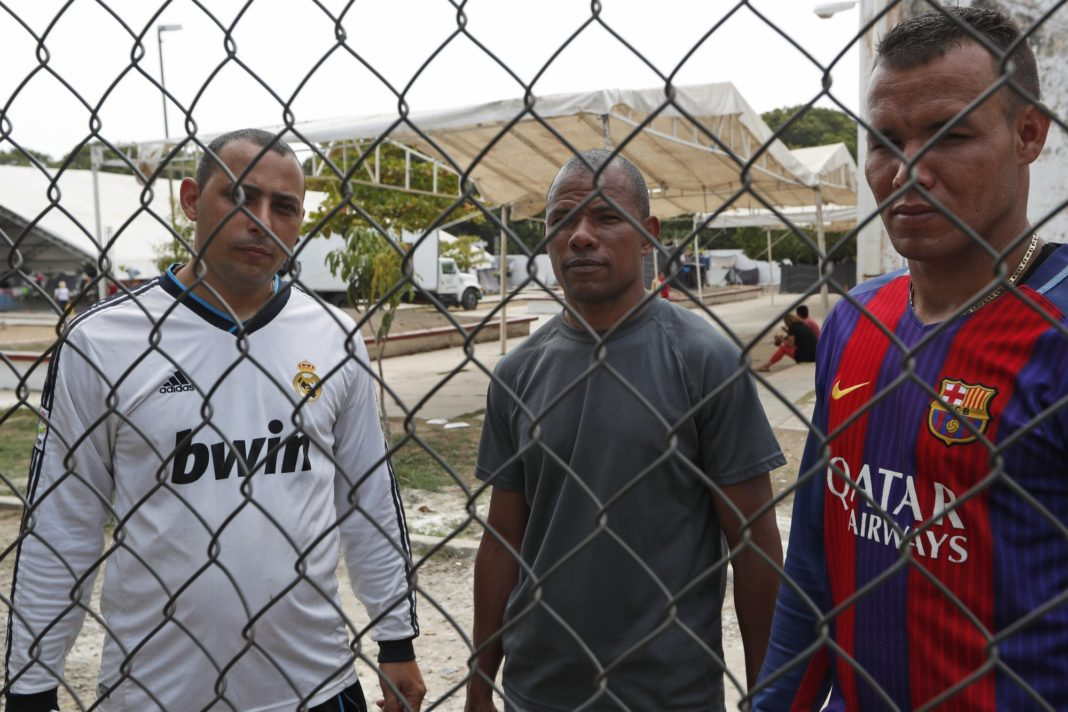 In this April 25, 2019 photo, Cuban migrants Jorge Luis Hernandez, left, Johan Diaz, center and Mike Garcia pose for photos inside a shelter set up in Mapastepec, Chiapas state. This group of migrants are waiting for humanitarian visas. They traveled from Cuba to Uruguay and from there by road to the state of Chiapas on the border between Mexico and Guatemala. (AP Photo/Moises Castillo)
