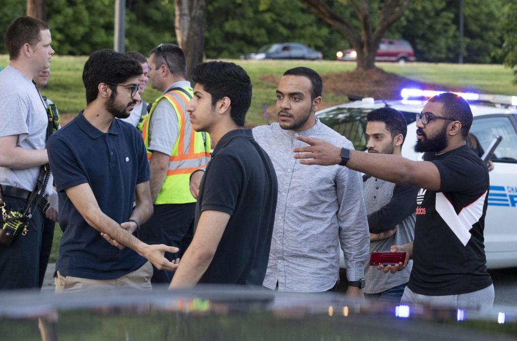 People gather across from the campus of University of North Carolina at Charlotte after a shooting at the school Tuesday, April 30, 2019, in Charlotte, N.C. The school shooting left at least a few people dead and several wounded Tuesday, prompting a lockdown and chaotic scene in the state's largest city. (AP Photo/Jason E. Miczek)