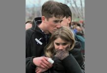 FILE - In this April 25, 1999 file photo, shooting victim Austin Eubanks hugs his unidentified girlfriend during a community wide memorial service in Littleton, Colo., for the victims of the shooting rampage at Columbine High School the previous week. Eubanks, who survived the 1999 Columbine school shooting and later became an advocate for fighting addiction has died. Routt County Coroner Robert Ryg said Saturday, May 18, 2019, that 37-year-old Eubanks died overnight at his Steamboat Springs home. A Monday autopsy was planned to determine the cause of death. (AP Photo/Bebeto Matthews, File)