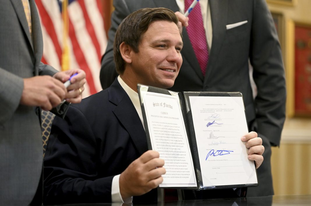 Florida Gov. Ron DeSantis holds up a bill allowing the import of cheaper prescription drugs from other countries after signing it, Tuesday, June 11, 2019, at the Eisenhower Recreation Center in The Villages, Fla. (Max Gersh/Daily Sun via AP)