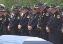 Officers honor the fallen hero. (Credit: WINK News)