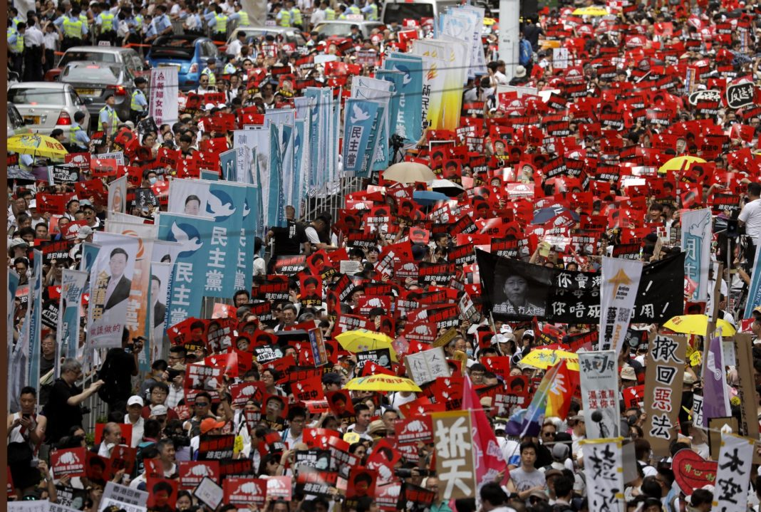 Protesters march along a downtown street against the proposed amendments to an extradition law in Hong Kong Sunday, June 9, 2019. A sea of protesters is marching through central Hong Kong in a major demonstration against government-sponsored legislation that would allow people to be extradited to mainland China to face charges.(AP Photo/Vincent Yu)