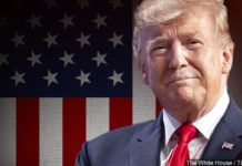 Trump in front of flag. (Credit: MGN)