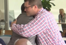 Men hug at the meeting. (Credit: WINK News)