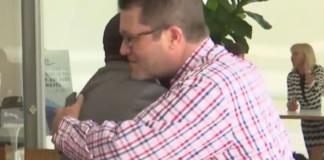 Men hug at the meeting. (Credit: WINK News)