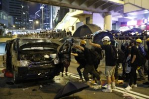 Protesters attack a van that apparently tried to drive at the protesters near a blocked road in Hong Kong, Sunday, July 21, 2019. (AP Photo/Vincent Yu)