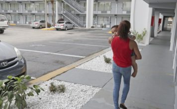 FILE - In this Sept. 10, 2018, file photo, Idalis Fernandez walks to her hotel room provided by FEMA with her son Adrian, 2, at the Baymont Inn in Kissimmee, Fla. Fernandez moved to Orlando from Puerto Rico after Hurricane Maria. (AP Photo/John Raoux, File)