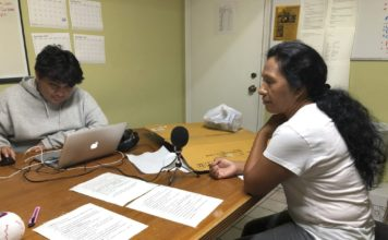 Natividad Jimenez, a volunteer at the Guatemalan-Maya Center, sits in front of a microphone listening to a message she recorded in an Ancient Maya language to urge immigrants to get water, cash, and gas and follow evacuation orders ahead of Hurricane Dorian on on Friday, Aug. 30, 2019 in Lake Worth, Fla. Charity groups are worried about vulnerable populations along the eastern coast, who were still in the cone of potential storm pathway forecast by the National Hurricane Center in Miami. (AP PhotoAdriana Gomez)