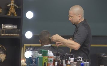 Ivan Suarez as he cuts the hair of a patron at his barber shop. (Credit: WINK News)